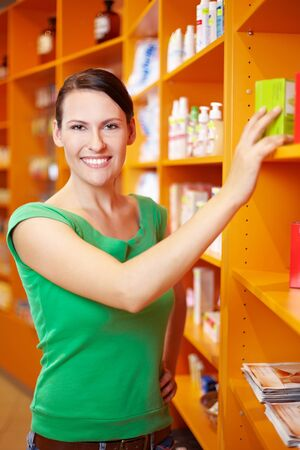 Happy smiling woman shopping for medicine in a pharmacy photo