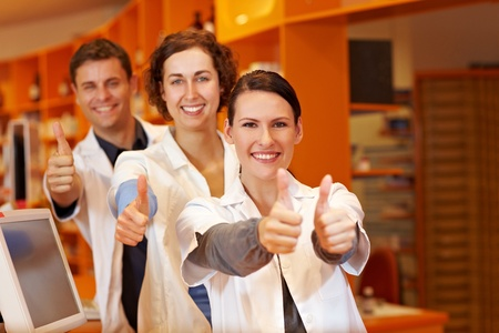 Three happy pharmacists holding their thumbs up in pharmacy photo