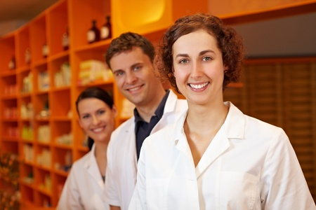 Three competent pharmacists smiling in a pharmacy photo