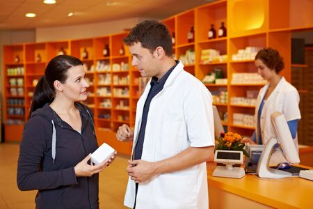 pharmacist: Pharmacist giving advice and selling to female customer in pharmacy Stock Photo