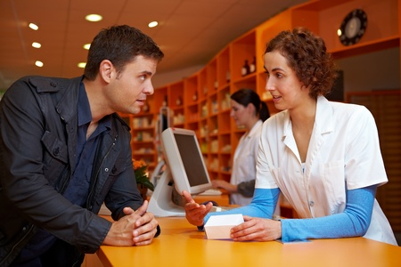 Discrete talk between customer and pharmacist in pharmacy photo