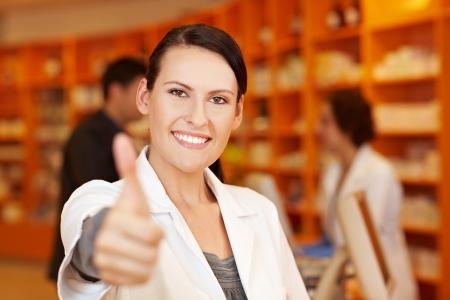 saleswomen: Happy pharmacist in pharmacy holding her thumb up