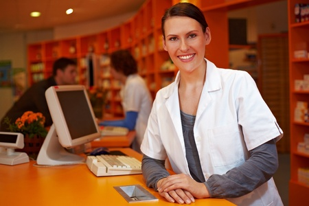 work experience: Kind female pharmacist behind counter in a pharmacy
