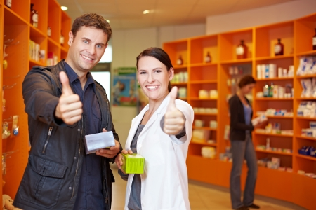 Happy customer and pharmacist holding their thumbs up in pharmacy