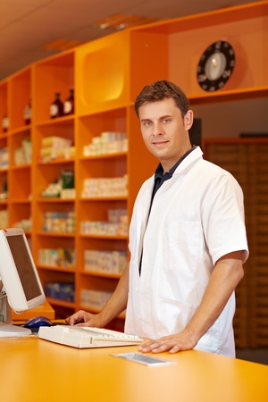 Pharmacist serving behind the counter of a pharmacy photo