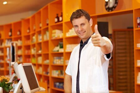 Smiling pharmacist holding his thumbs up in a pharmacy photo