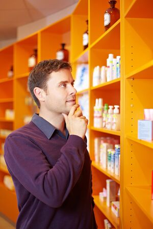 price uncertainty: Pensive man buying some medicine in a pharmacy