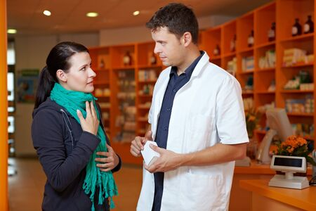 Woman with sore throat in pharmacy talking to pharmacist photo