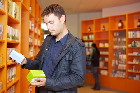 price uncertainty: Man comparing two medical products in a pharmacy