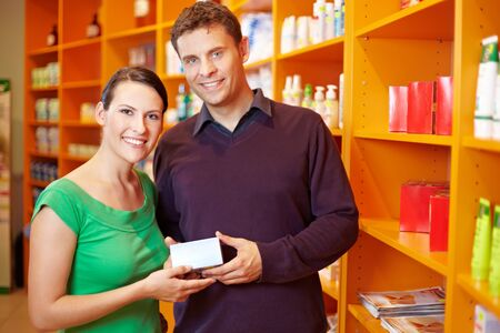 Happy couple shopping for medication in a pharmacy photo