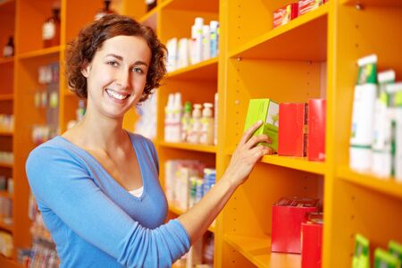 Customer at shelf in drugstore looking for medicine photo