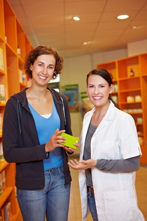 Customer getting a recommendation from a pharmacist in drugstore Stock Photo - 11031597