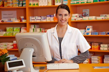 saleswomen: Happy pharmacist standing at checkout counter in a drugstore