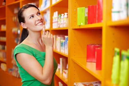 Content woman shopping in pharmacy and looking at shelves photo