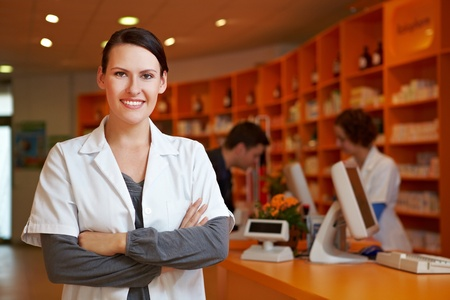 Happy pharmacist with her arms crossed in a pharmacy Stock Photo - 11031640