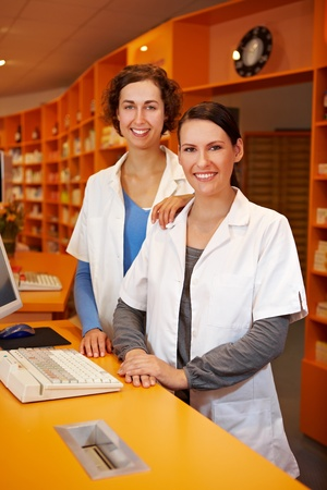 Smiling pharmacist trainee in drugstore with a pharmacist photo