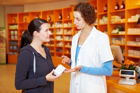 Pharmacist selling medicine to customer in a drugstore photo