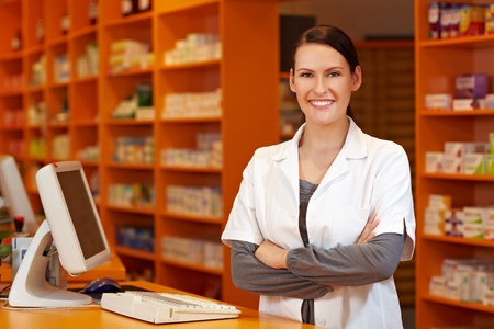 pharmacy technician: Happy pharmacist with her arms crossed at checkout in pharmacy