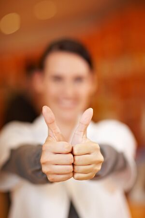 Happy pharmacist holding two thumbs up in drugstore photo