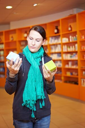 Woman comparing two different products in a pharmacy photo