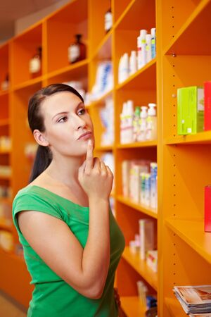 pharmacy store: Pensive woman in pharmacy thinking while looking at shelf Stock Photo