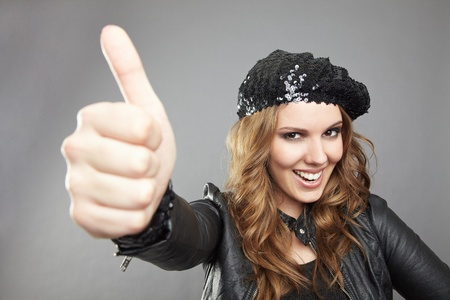 Happy female winner holding her thumbs up