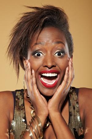 cara sorprendida: Joven y feliz mujer africana con estilo que parece sorprendida