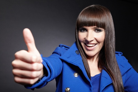 Happy young smiling woman holding her thumbs up Stock Photo - 11396207
