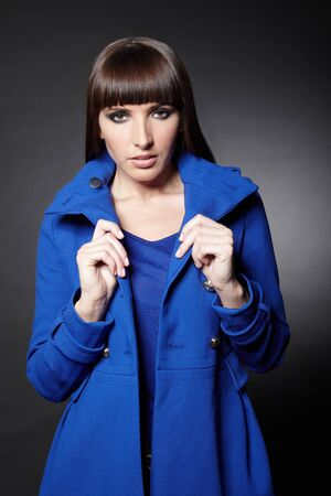 horse collar: Young woman holding the collar of her blue coat Stock Photo