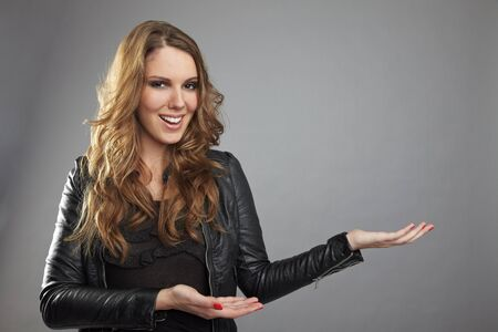 Happy woman showing imaginary product with her hands photo