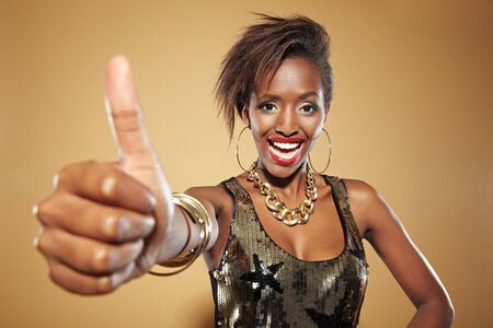 Young fashionable african woman lifting her thumb up photo