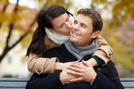 cheek: Woman in love kissing happy man in park on cheek Stock Photo