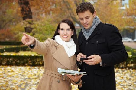 tour guide: Los turistas en viaje a la ciudad con smartphone y mapa de la ciudad