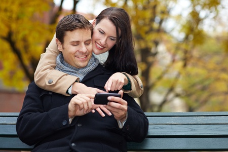 Happy man and woman using smartphone in autumn park photo