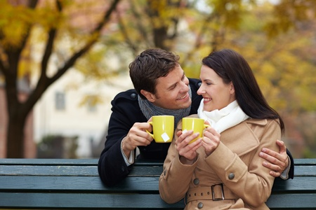 Happy couple drinking tea in a fall park photo