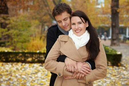 Happy man leaning on attractive woman in autumn park