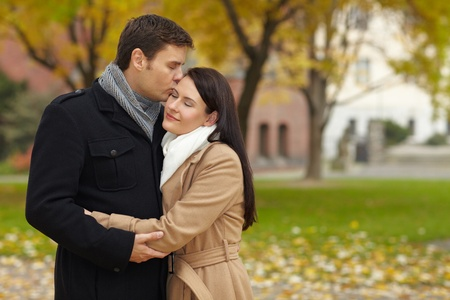 smooch: Man giving woman a romantic kiss in an autumn park