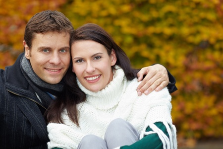 Portrait of a smiling couple embracing in fall photo