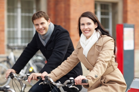 Smiling couple riding on bicycles in a city photo