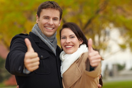 acknowledgment: Happy couple in fall park holding their thumbs up