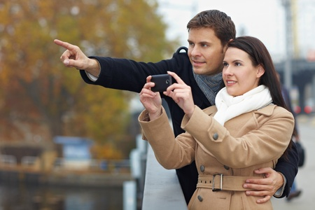 Couple on city trip taking pictures with mobile phone photo