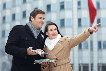 winter break: Happy tourists on sightseeing trip with tour guide and city map