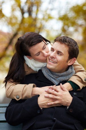 smooch: Woman in love kissing happy man in park on cheek Stock Photo