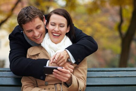 Happy couple using Social Media with a smartphone photo