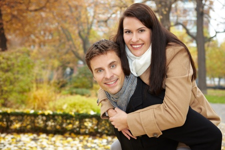 fit couple: Happy couple doing a piggyback ride in a fall park