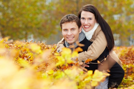Happy man carrying smiling woman piggyback in fall photo