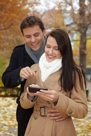 Happy couple in autumn using a smartphone Stock Photo - 11638467