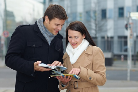 winter break: Happy tourists on holiday with tour guide and city map