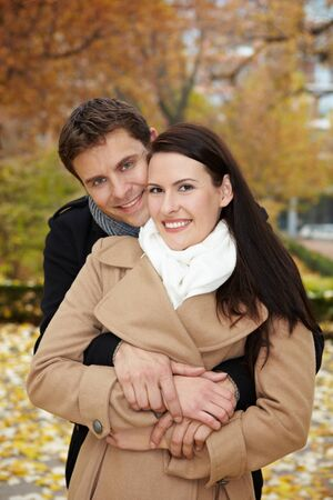 Happy smiling couple embracing in a fall park photo