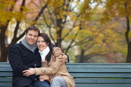banc parc: Heureux couple souriant sur un banc de parc � l'automne